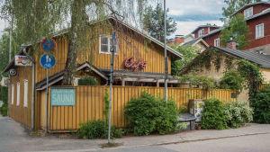 Keltainen puutalo kadunkulmassa, kyltti Rajaportin sauna, ympärillä puutaloja
