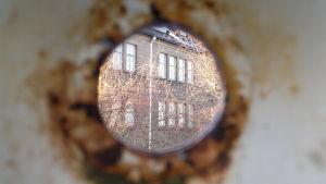 Gamla fängelsebyggnader på Kakolabacken fotat genom ett hål i en vägg.