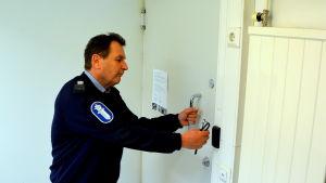 Polis vid dörren till polishäkte.