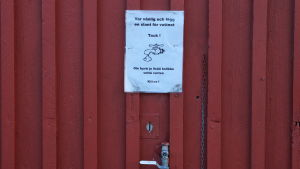 Vattenpost på rödmyllad utomhusvägg
