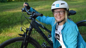 Malin Valtonen poserar vid en cykel med en vit cykelhjälm på huvudet.