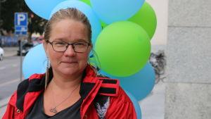 Nuorehko nainen ilmapallojen edessä Turun pääkirjaston ulkopuolella.