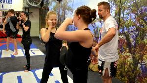 Två kvinnor tränar thaiboxning inne i en träningslokal.