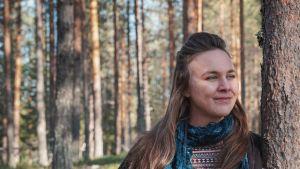 Pitkähiuksinen nainen nojaa puunrunkoon, katsoo ohi kameran oikealle