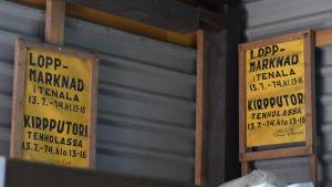 Två skyltar på en vägg av plåt. På skyltarna står det att det ordnas Loppmarknad i Tenala. Skyltarna är från 1974.