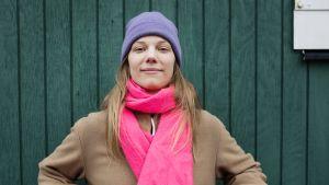 Vit kvinna med lila mössa och rosa halsduk står framför en grön vägg.