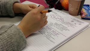 En student gör anteckningar i sitt häfte på två språk.