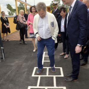 President Sauli Niinistö hoppar hage utanför ett daghem i Björneborg, där han och Jenni Haukio invigde Bostadsmässan 2018. Många människor ser roat på.