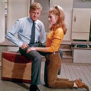 Mies ja nainen tyhjässä asunnossa: mies istuu matkalaukun päällä ja nainen on polvillaan lattialla. Robert Redford ja Jane Fonda elokuvassa Paljain jaloin puistossa.