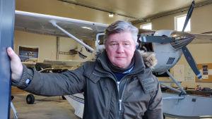 En man håller upp dörren till en hangar. Bakom honom syns ett litet flygplan.