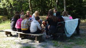 Lägerdeltagare och ledare på Prometheus-lägret i Lojo sitter på bänkar på en gård och diskuterar.