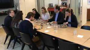 Kolleger äter lunch tillsammans vid ett matbord på kontoret.