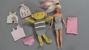 Två dockor ligger på bordet omgivna av dockkläder tillverkade av avlagda strumpor