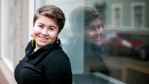 En kvinna klädd i svart med kort, mörkt hår står lutad mot ett skyltfönster. Hon ser in i kameran och ler. I fönstret bakom henne ser man hennes spegelbild.