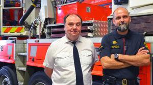 Anskaffningschefen och jourhavande brandmästare bredvid ett utryckningsfordon.