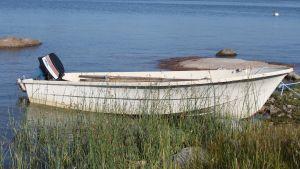 En vit liten glasfiberbåt med motor.