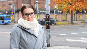 Mia Rintasalo i grå rock med vit stor halsduk, i bakgrunden gata med buss och bil.