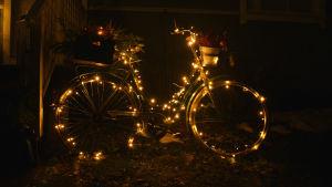 En cykel dekorerad med en ljusslinga lyser upp mörkret.
