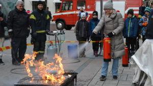 Nina Hyvönen, lärare vid Cygnaeus skola i Åbo, använder en brandsläckare.