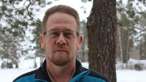 Jesper Sunström i uteomhusmiljö, snö och och tallar i bakgrunden, i blå fleecejacka