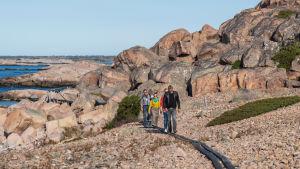 Ihmisiä kävelemässä pitkospuita pitkin pirunpellon yli. Taustalla näkyy kalllioita ja merta.