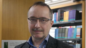 Docent Tom Bergroth framför en bokhylla