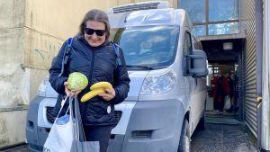 En glad kvinna tittar ner på ett kålhuvud och en banan som hon har i händerna. Hon står framför en bil som är framför ett hus. I dörröppningen bakom henne syns en man längre bort.