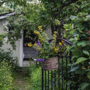 Blommor i korg hänger på en svart järnport som öppnar sig mot en lummig trädgård. I bakgrunden en ljusmålad trästuga.