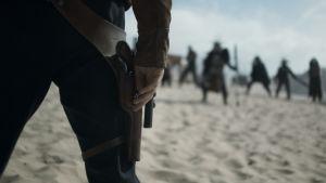 Närbild på Han Solos (Alden Ehrenreich) hand just innan han skall dra sitt vapen.