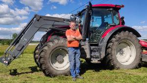 En man står bredvid en traktor på en åker.