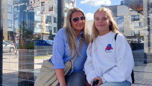 En lite äldre och en ung kvinna sitter på en bänk i en busskur. Se ler och tittar in i kameran.