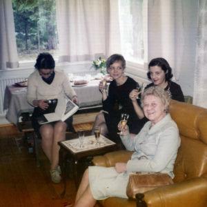 Kolme naista istuvat tuoleilla kuohuviinilasit kädessään. Neljäs tummahiuksinen lukee kirjaa.