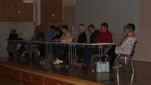 Flera personer som sitter på rad i en panel.