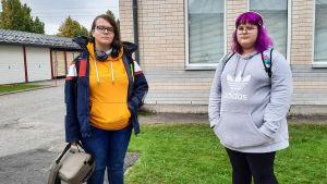 Två unga kvinnor står på en skolgård.