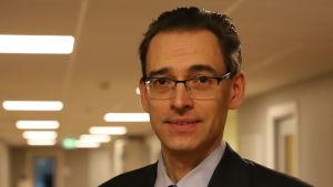 En mörkhårig man i skjorta, slips och mörk kostymrock och glasögon står i Etlas korridor.