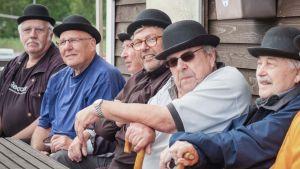 Knallipäisiä miehiä istumassa