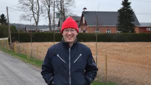 Erik Perklen med en stubbåker och gården Postis i bakgrunden december 2020.