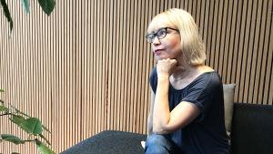 Katja Tikka sitter och tittar ut genom fönstret.
