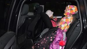 två små barn i baksätet av en bil. Det är mörkt och regnigt ute.
