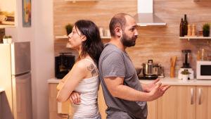En kvinna och en man står rygg mot rygg i ett kök.