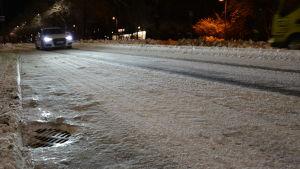 En vit bil kör på en snöig och isig gata.