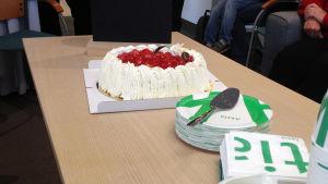 Jordgubbstårta på ett bord tillsammans med pappersassietter, pappersmuggar och servetter där det står Aktia.