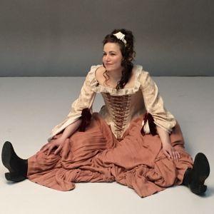 Julia Korander sitter bredbent på golvet i 1700-talskläder.