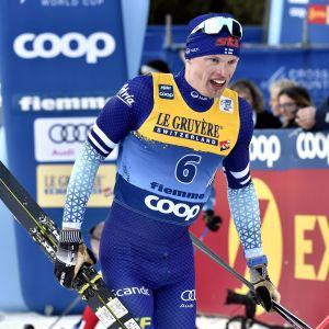Iivo Niskanen håller i skidor och stavar efter målgång.