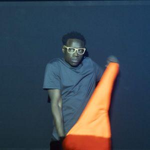 En man står på en mörk scen med en neonröd arbetsrock i handen.