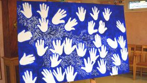 En stor tavla med blå bakgrund med vita handavtryck.