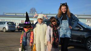 Fyra barn, två är utklädda till påskhäxor och två är utklädda till påskharar.