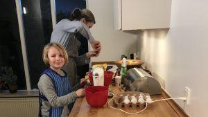 Lotta Nymann-Lindegren bakar hemma i köket tillsammans med sin son Aksel.