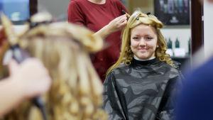 Nicole Nybergs blonda hår blir lockat av en frisörstuderande.
