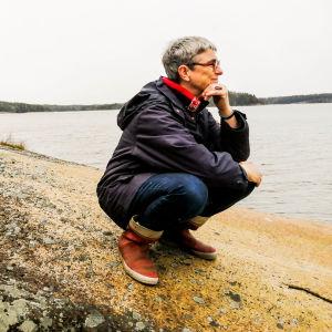 En medelålders kvinna på en strand tittar ut mot havet, ser glad och fundersam ut.